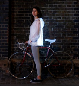 Custom embroidery: girl wearing LED jacket standing next to bike.